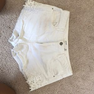 White jean shorts with lace on the sides.